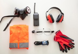 Work safety protection equipment flat lay. Industrial protective gear on white background. Construction site health and safety concept, top view.