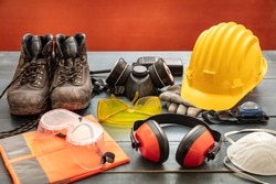 Work safety protection equipment. Industrial protective gear on wooden table, red color background. Construction site health and safety concept