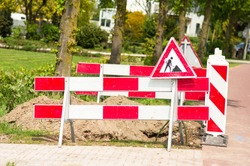 Work site closed with barriers and sign for roadworks