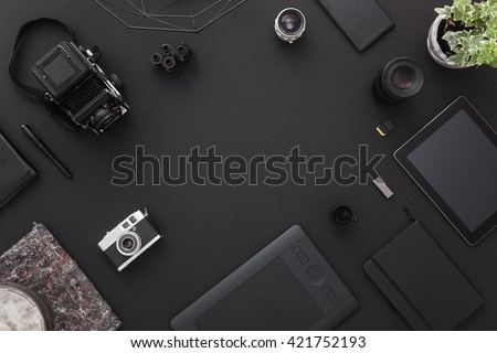 Work space on black table of a creative designer or photographer with laptop, tablet, cameras other objects of inspiration and copy space. Stylish home studio concept of technology trends.