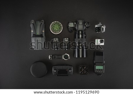 Work space photographer with laptop, digital camera, memory card, action camera, drone, remote controller, phone, triggers and camera accessory. Top view on black table background.  Mockup template