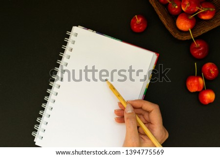 Work space with notebook and red apples on black chalk board background. Female hand holds a pencil and writes plans in the diary. View from above. From above. #1394775569