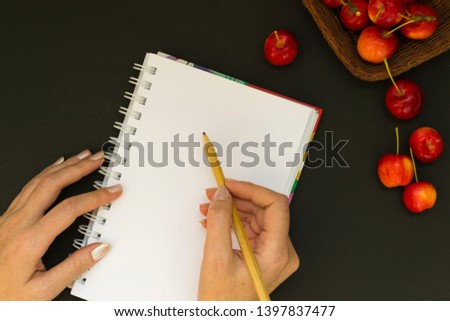 Work space with notebook and red apples on black chalk board background. Female hand holds a pencil and writes plans in the diary. View from above. From above. #1397837477