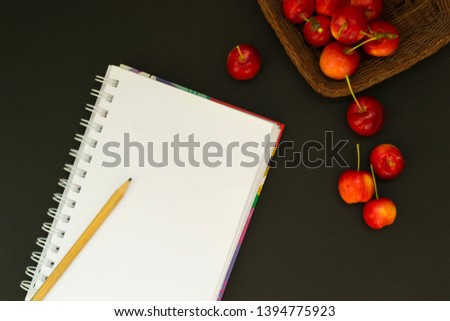 Work space with notebook and red apples on black chalk board background. View from above. From above. #1394775923