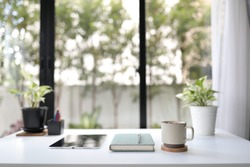 Work station with coffee mug and notebook and tablet decorating with green plant home office