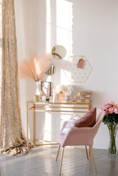 Work table in a bright room. Feminine space stylish interior. Boudoir makeup table. Delicate tones.
