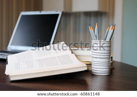 work table with computer notebook,pencil, book in a home