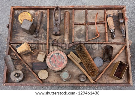 work table with old tools of the artisan shoemaker for repair, cleaning, polishing and finishing shoes