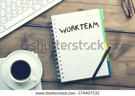 work team text on notebook with keyboard and coffee on desk