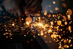 Work with a grinder for metal. Sparks from metal friction. A worker is grinding a part. Steel processing with an electric tool. Creation of the structure in the workshop.