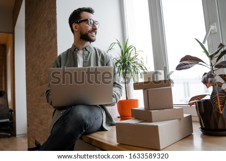 Work with laptop, bearded male entrepreneur. Young small business owner, selling online on a website. Online Sales, E-Commerce, Online Business, with postal parcel, selling online, delivery concept.