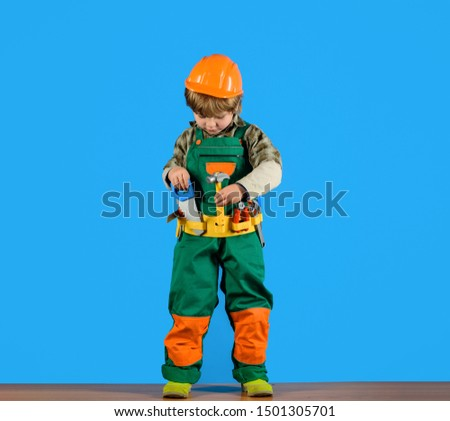 Work with tools. Little boy in builder's uniform with repair tools. Repair. Boy as builder or repairer. Tools for building. Builder boy in helmet and tools. Little repairman with tool belt. Child game