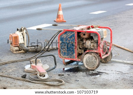 work zone with special equipment - hydraulic driven grinder machine and leaf blower - during roadworks