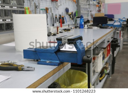 Workbench of a workshop and a blue vise to repair - Shutterstock ID 1101268223