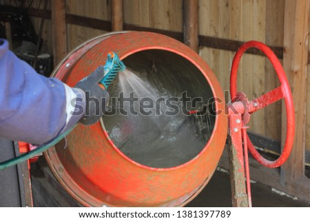 Worker adds water to the red cement mixer #1381397789