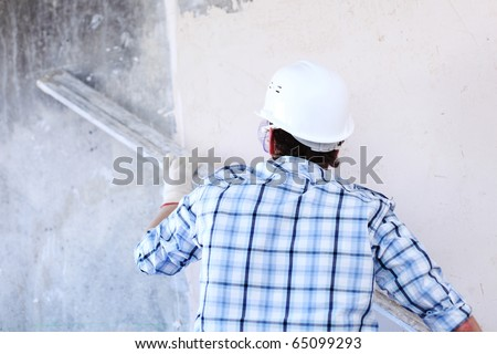 worker aligns wall