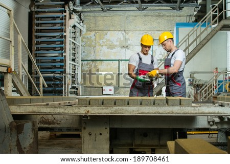 Worker and foreman in a safety hats performing quality check on a factory