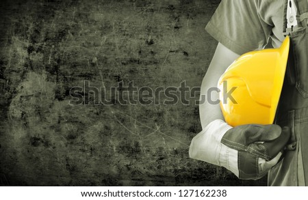 Worker and grunge texture in background. Concept of OSH (occupational safety and health) - stock photo