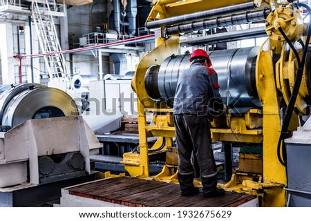 Worker and stock with rolls of sheet steel in industrial plant