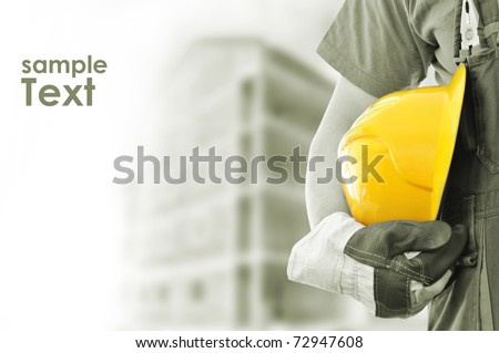 Worker and the blurred construction in background with space for your text - stock photo