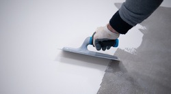 Worker applying a white epoxy resin bucket on floor