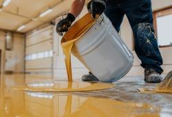 Worker applying a yellow epoxy resin bucket on floor.