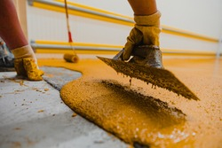 Worker applying epoxy and polyurethane flooring system.These easy-to-clean products also have non-slip features.