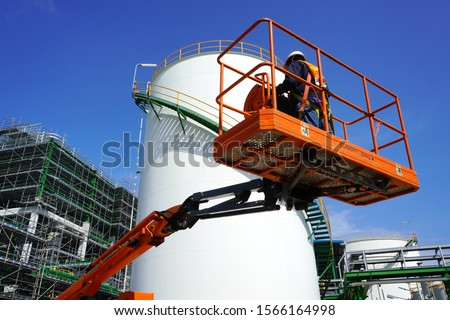 Worker are driving the Orange articulate boom lift or telescopic boom lifts and bucket crane mounted on truck to safety for working at heights and articulating boom lift reaching high up.
