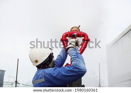 Worker are test the fire hose valve to connect the fire hose at construction site in chemical plant as part of emergency drills.