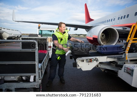 Worker Arranging Luggage On Trailer Connected To Airplane
