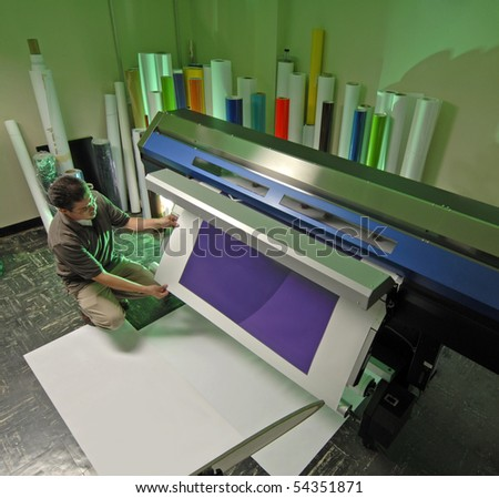 Worker at a large Inkjet printer