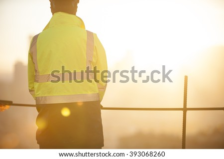 Worker at the construction site and sunrise background