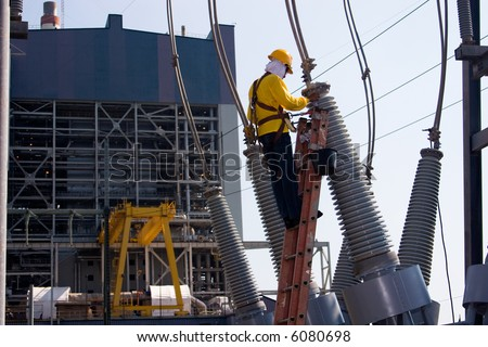 Worker at the switch yard for maintenance work with power plant at the background