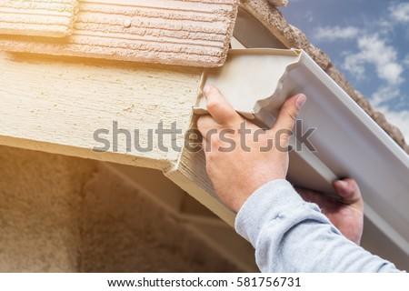 Worker Attaching Aluminum Rain Gutter to Fascia of House.