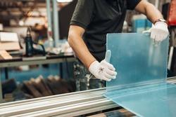 Worker bends plastic detail at the workshop