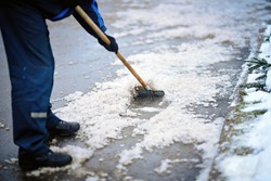 Worker breaking ice with hand ice breaker tool, cleaning ice with razor scraper on the sidewalk. Worker in uniform cleaning ice and snow with icebreaker tool. Janitor cleans area. Snow removal
