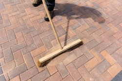 Worker brushing kiln dried sand in to joints of newly laid block paving on a driveway