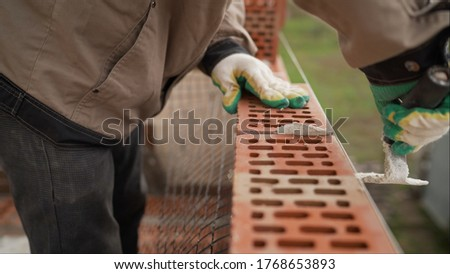 Worker builds a wall of colored brick. Worker in Close up of industrial bricklayer installing bricks and mortar cement brick on construction site