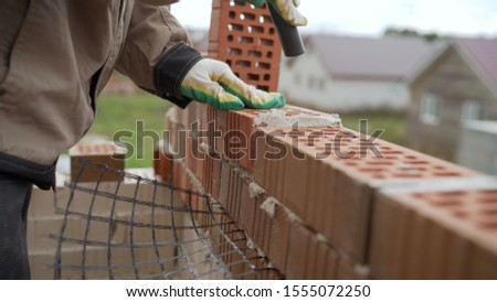 Worker builds a wall of red silicate brick.. Bricklayer build walls in accordance with construction plans #1555072250
