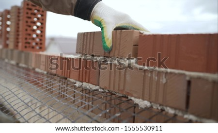 Worker builds a wall of red silicate brick.. Bricklayer build walls in accordance with construction plans #1555530911