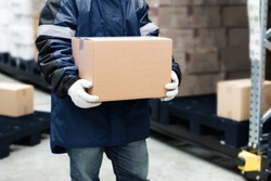 Worker carrying a goods box in a large frozen warehouse.Export-Import Logistics system concept.