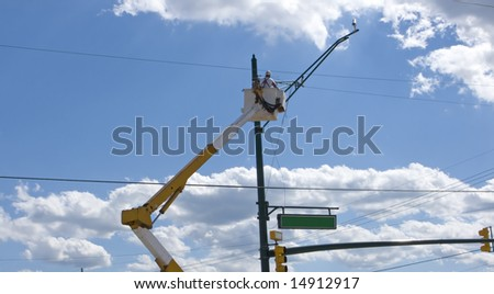 worker changing light fixture on a post