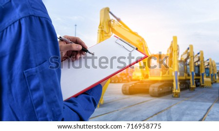 Worker checking document in front of the mechanical excavator at yard  for import export business.