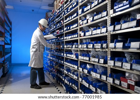 Worker checking inventory in stock room of a manufacturing company