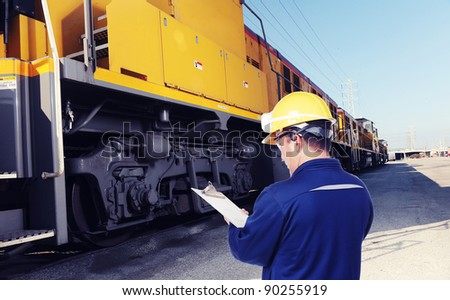 worker checking on train machine