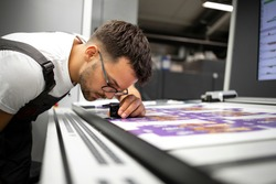 Worker checking print quality of graphics in modern printing house.
