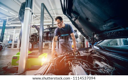 Worker checks and adjusts the headlights of a car's lighting system. Auto repair service. #1114537094
