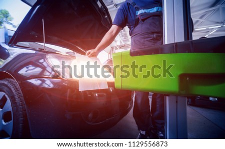 Worker checks and adjusts the headlights of a car's lighting system. Auto repair service. #1129556873