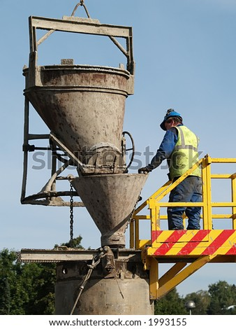 Worker checks cement pouring into the well, close-up