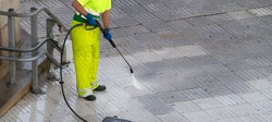Worker cleaning a street sidewalk with high pressure water jet. Urban maintenance concept. Copy space